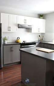painted kitchen cabinets with white and benjamin moore chelsea gray gray owl subway tile red toned wood flooring and black laminate countertops