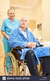 Geriatric Nursing Senior As A Patient In A Wheelchair With Nurse In Geriatric