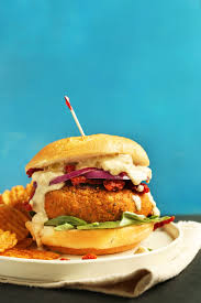 plate of our sun dried tomato herbed pea burger recipe served with chips