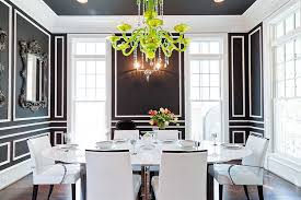 elegant black and white dining room with oval table and green chandelier lights