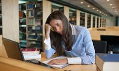 Female student in library  Writing a PhD thesis