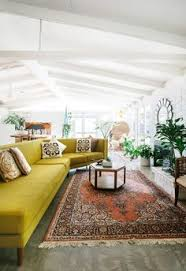 this is a large living e the slated wood ceilings painted white make it look even more expansive i also like the chic boho feel of the decor