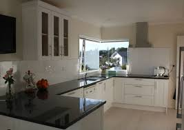 browns bay solid timber shaker cabinetry finished in white provides a crisp feel to a modern browns bay home a bulkhead was constructed to frame the