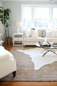 family room rugs white cow hide rug layered on top of a jute rug in a family room rugs