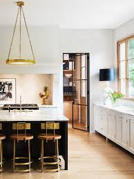 beautiful modern kitchen with brass counter stools pendant and table lamp with black shade