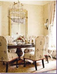 alessandra branca dining chairs slipcovered in ilis embroidered linen the giltwood mirror is louis xvi and the droll bronze and crystal chandelier is