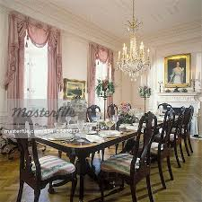 dining rooms queen anne chairs long mahogany dining table set for dinner with crystal fl centerpiece crystal chandelier formal pale pink walls