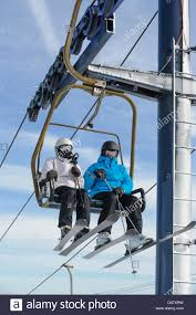 two skiers riding ski lift chair in close up man and woman with sunlight and fair weather sky background copy space