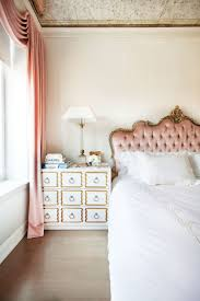 An old-world inspired bedroom with a pink upholstered headboard, pink  tapestries, and