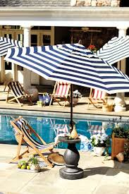 white striped patio umbrella: poolside patio with striped umbrella and chairs