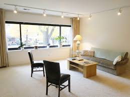 image modern track lighting. cozy sofa and simple chairs installed at living room illuminated by modern track lighting above it image o