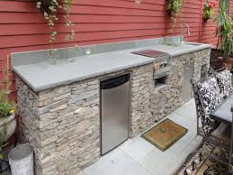 prefab modular outdoor kitchen kits with concrete countertop electric stove under decorative vines padded chairs and rectangle table