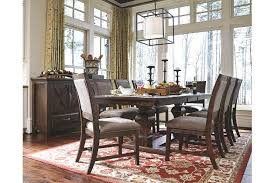 this dining table features a beautiful double pedestal acpanied by upholstered chairs