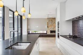white kitchen dark tile floors. This Open Kitchen Utilizes The Large Windows To Brighten Up Space, Counterbalancing With White Dark Tile Floors