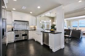 white coastal kitchen decor with white wooden kitchen cabinet and black granite countertop also stainless steel cooktop on dark brown laminate kitchne