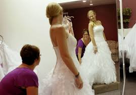 morghan spychalski and paige lacourse laugh as spychalski tries on a moonlight wedding dress at dream