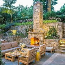 sloped backyard designs stone patio fireplace