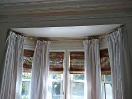 bay window curtain rods with white curtain and roman blinds