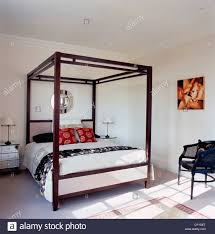 black white style modern bedroom silver. A Modern White Bedroom With Four Poster Bed, Silver Chest Of Drawers, Black Wicker Chair Style S