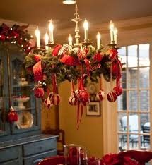 decorate a usual chandelier with evergreen branches red ribbon and ornaments