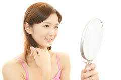 Happy Beautiful Young Woman Holding Mirror And Lipstick Stock Photo