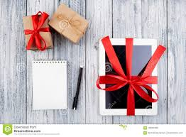 gifts and a tablet wrapped in a red ribbon a paper notepad a pen