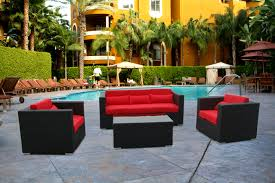 affordable black wicker patio furniture set with red cushions and rectangular glass top coffee table on concrete pool deck