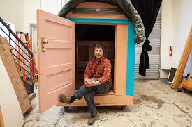artist and designer gregory kloehn sits in the doorway of his latest tiny house which artist creates mobile homes