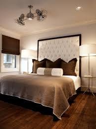 Nest Interior Design Gray & chocolate brown masculine bedroom with tall  custom white tufted headboard, Jonathan Adler Meurice floor lamps, brown  roman shade ...