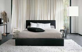 elegant bedroom with black cushioned bed on white area rug also corner stand lamp