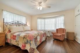 large bedroom overlooking the back yard with bamboo flooring ceiling fan and two closets