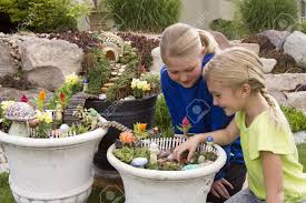 stock photo two young girls helping to make fairy garden in a flower pot outdoors