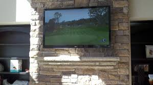 hang a flat screen tv on a stone wall over a fireplace