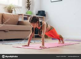 little girl doing plank exercise at home stock photo
