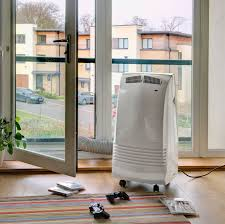 air conditioning portable unit. gree 3.5kw portable air conditioner in a lounge with hose going out the balcony conditioning unit