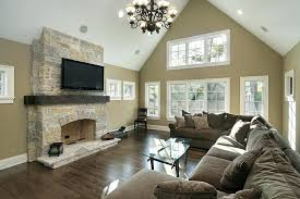 beige walls white ceiling vaulted ceiling and sculpted metal chandelier hang above a wide expanse of plush cushioned brown sectional