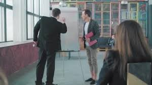 Two Managers Hold A Presentation In The Audience Near The Flipchart Draw Charts And Discuss Creative Office Interior Coworking Team Office Workers