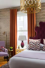 a uniquely shaped burdy headboard and long burnt orange curtains are tied together with squiggly