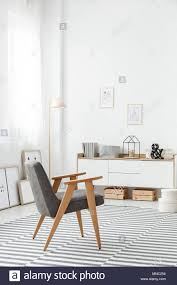 wooden crates under a white sideboard and a comfortable modern gray armchair in a stylish living room interior with a striped rug and white wall