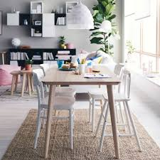 a bright dining area with a dining table in ash veneer and four white dining chairs one of them is a junior chair