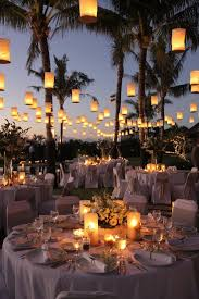 outdoor wedding lights decorations with round tables and white covered chairs under hanging lanterns