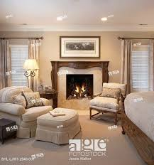 stock photo master bedroom sitting area monochromatic white and cream color theme rococo style wood fireplace mantel gas fire windows on either side