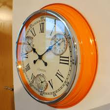 large round wall clock with orange case cream face black roman numerals and 3
