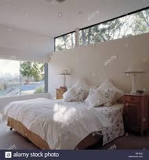 Schmale Fenster über Dem Bett Mit Weißen Kissen Und Quilt In Hellen