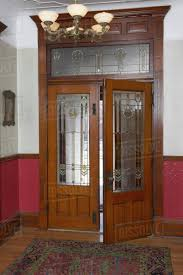 arts and crafts front entry french doors with leaded and stained glass transom detailed architectural trim dado lower wall covered in molded tin
