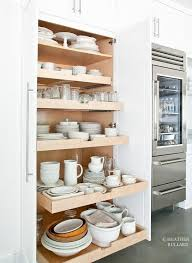 sweet cottage kitchen features a glass front refrigerator ex to a pantry fitted with pull out shelves