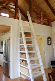 A sleeping loft off the kitchen, with a ladder that has built in storage.