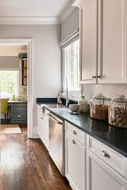 white shaker cabinets with quartz countertops. long kitchen pantry with white cabinets and black quartz. off shaker beadboard trim backsplash quartz countertops o