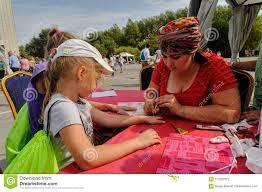 художник прикладывая татуировку хны на руке девушки Tyumen