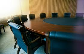 meeting room containing a large roundtable with many chairs around it